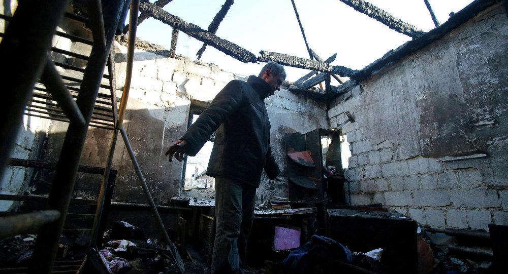 Hombre en su casa dustruida en Donetsk