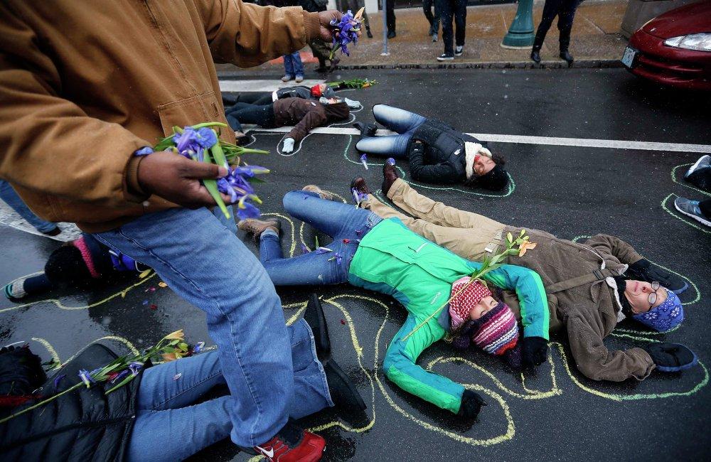 Люди лежат на земле в очерченных мелом контурах во время акции протеста по случаю 100-й день смерти Майкла Брауна