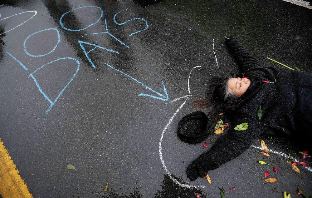 Женщина лежит на земле в очерченных мелом контурах во время акции протеста по случаю 100-й день смерти Майкла Брауна