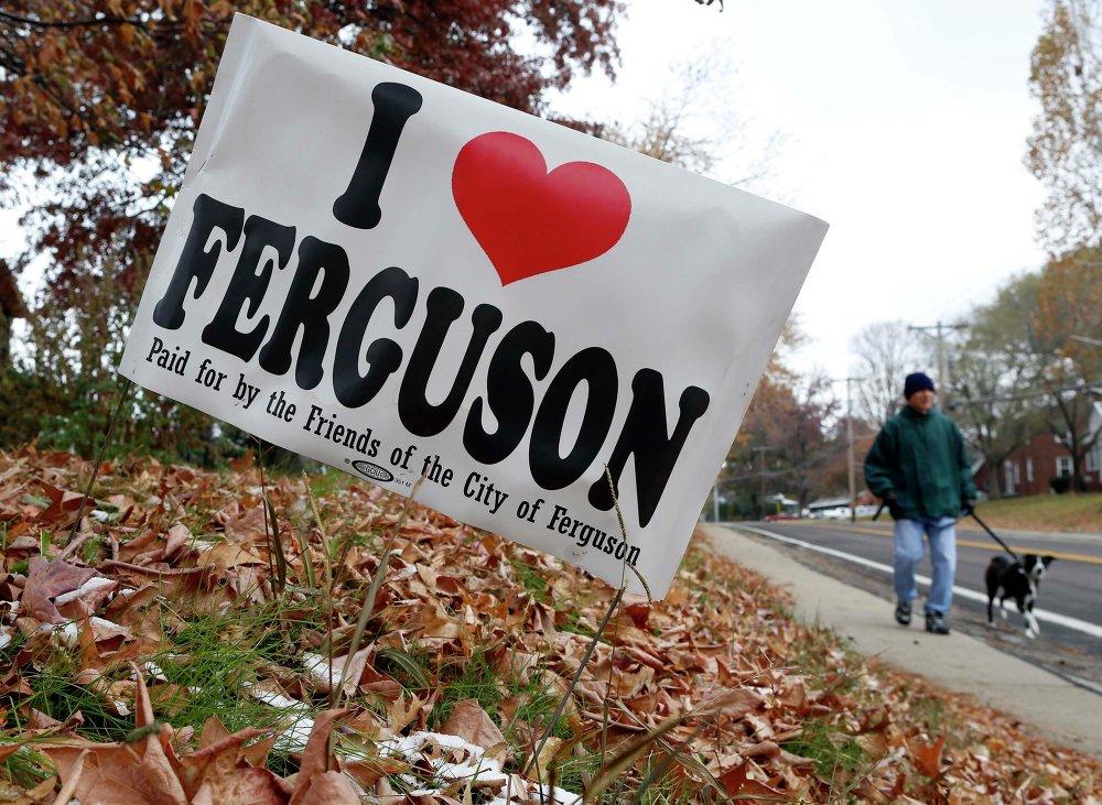 Человек на фото мимо знака I Love Фергюсона, по улице в Фергюсоне