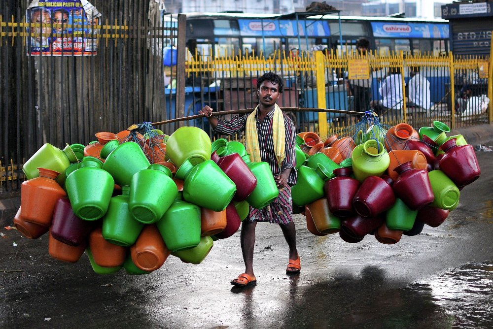A man carries empty water pitchers for sale in a market in the southern Indian city of Bangalore October 9, 2014.