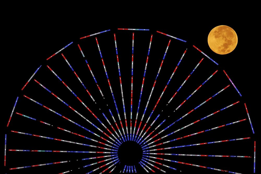 The moon is pictured behind a ferris wheel on the pier in Santa Monica, California after a total lunar eclipse, also known as a blood moon, October 8, 2014.