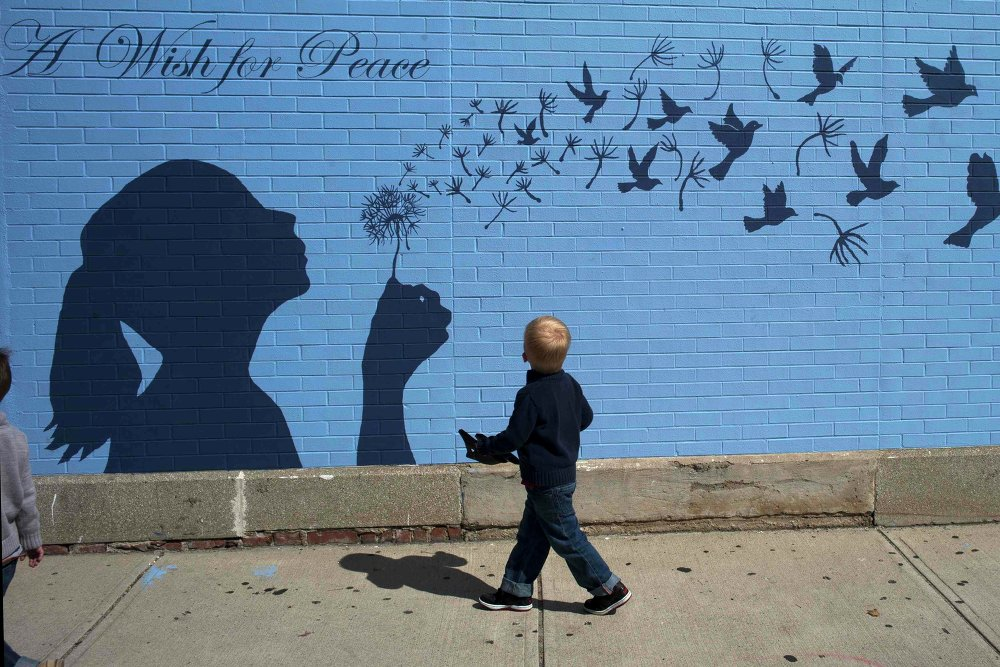 A boy looks up at a mural reading A Wish for Peace in Medford, Massachusetts September 15, 2014.