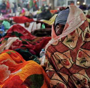 Un pasajero indio se cubre del frío en una estación de tren