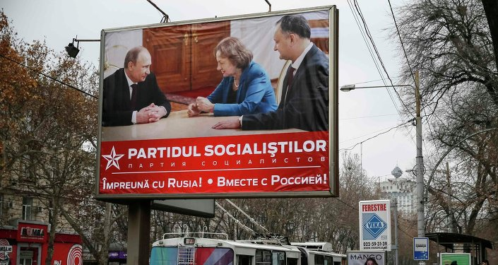 People walk near a pre-election poster for the Party of Socialists, with a picture of party members meeting with Russian President Vladimir Putin, in Chisinau November 29, 2014.