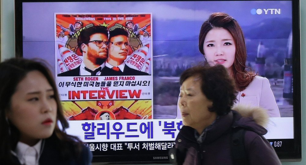 People walk past a TV screen showing a poster of Sony Picture's The Interview in a news report, at the Seoul Railway Station in Seoul, South Korea, Monday, Dec. 22, 2014