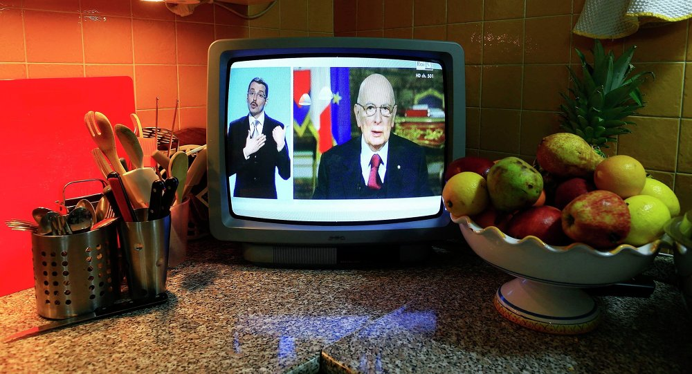Italian President Giorgio Napolitano (R) is seen in a television as he delivers his speech to Italians in Rome December 31, 2014