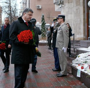 Ukraine's President Petro Poroshenko lays a bouquet of flowers with other mementos left for the victims of the shooting by two Islamist gunmen at the Paris offices of the satirical French newspaper Charlie Hebdo, outside the French embassy in Kiev January 9, 2015.