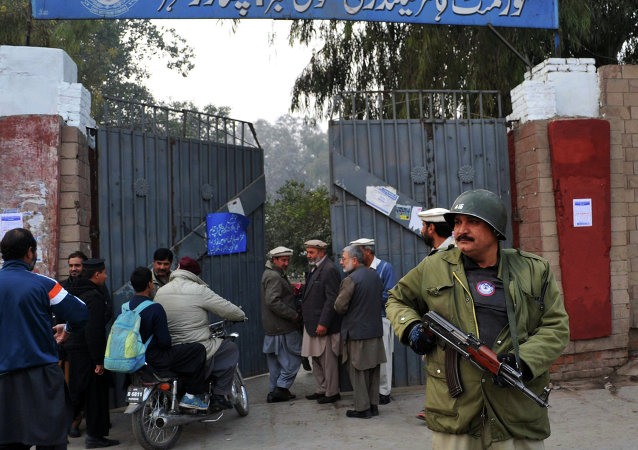 A Pakistani policeman stands guard outside a government school after schools in the city reopened following a Taliban attack in Peshawar on January 12, 2015.