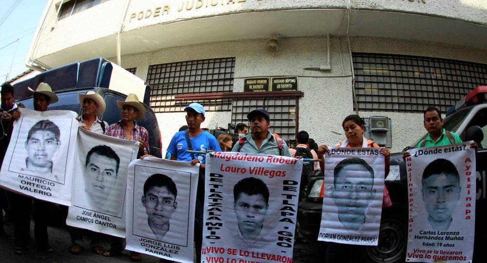 Familiares sostienen carteles de los 43 estudiantes desaparesidos