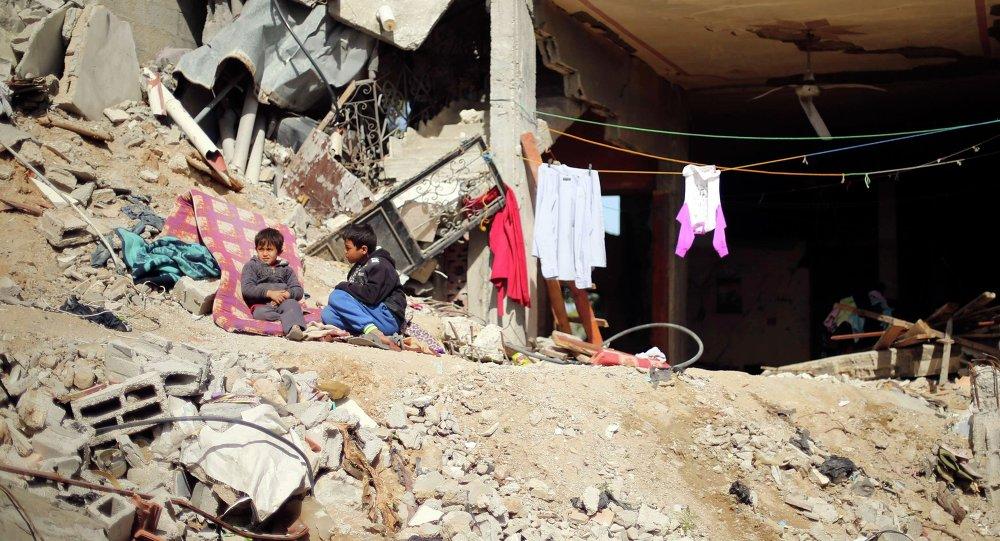 Chicos palestinos sientan fuera de su casa dañada