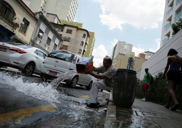 Hombre vierte el exceso del agua del río en la carretera después de llenar su barril en Sao Paulo
