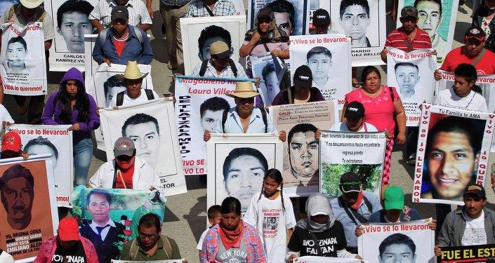 Familiares sostienen carteles de los 43 estudiantes desaparesidos en Guerrero, México
