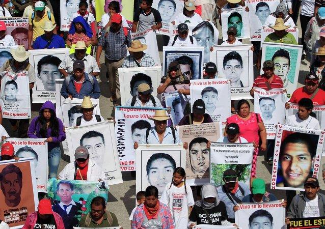 Familiares sostienen retratos de los 43 estudiantes desaparesidos en Guerrero, México