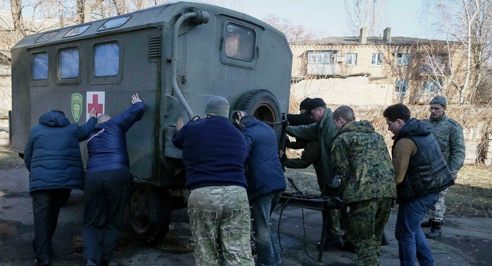 Miembros de un hospital móvil empujan un remolque médica en Artiómovsk