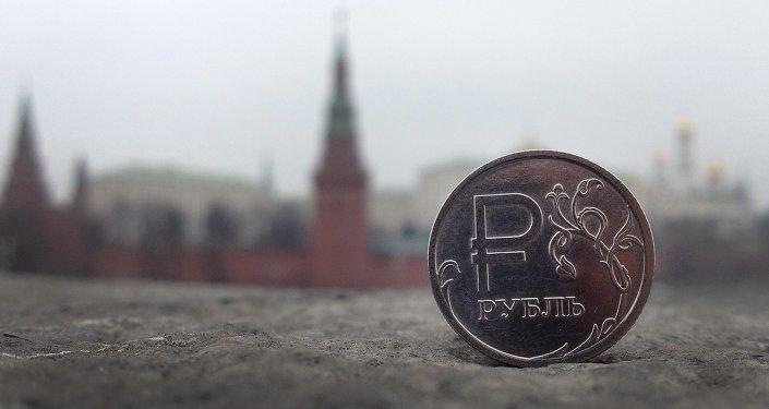 Una moneda de rublo con el Kremlin de Moscú de fondo