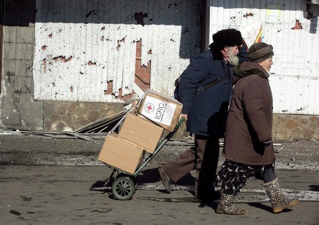 Hombre y mujer con paquetes de la Cruz Roja, Debáltsevo, 22 de febrero, 2015
