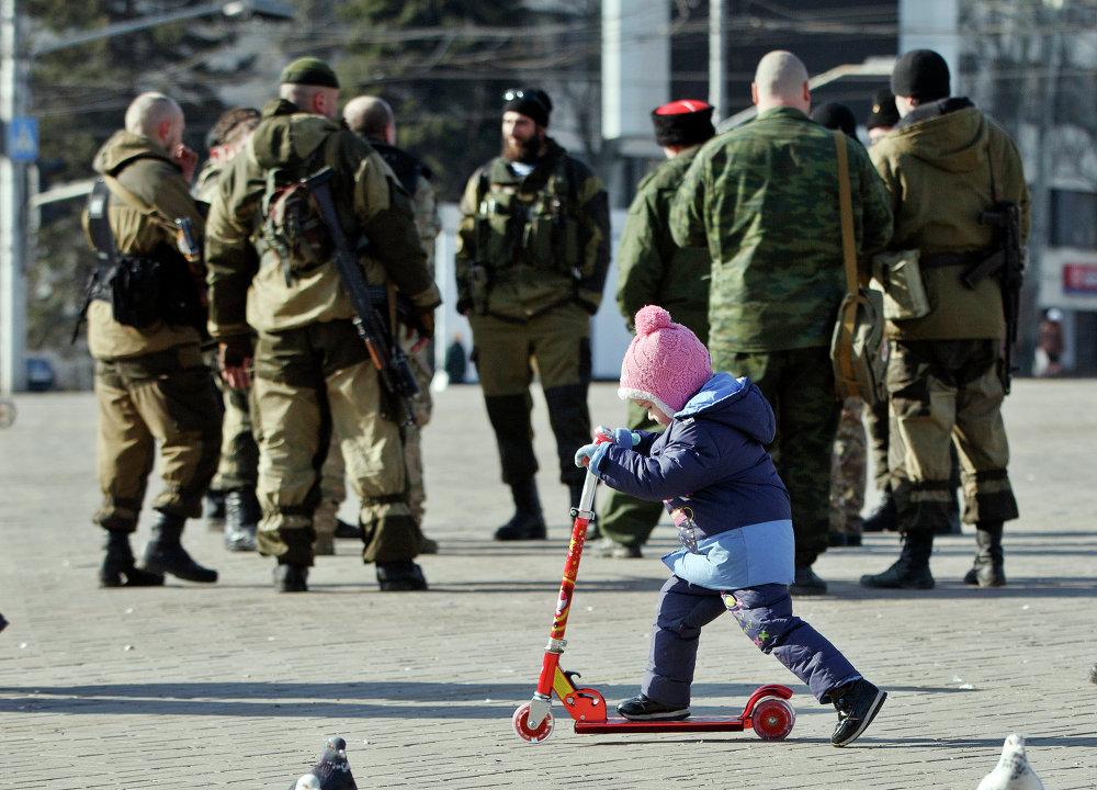 Un niño juega cerca de los milicianos de la República Popular de Donetsk
