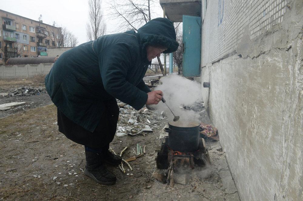 Una mujer preparando comida sobre fogata a la entrada de un edificio residencial  dañado por operaciones de combate