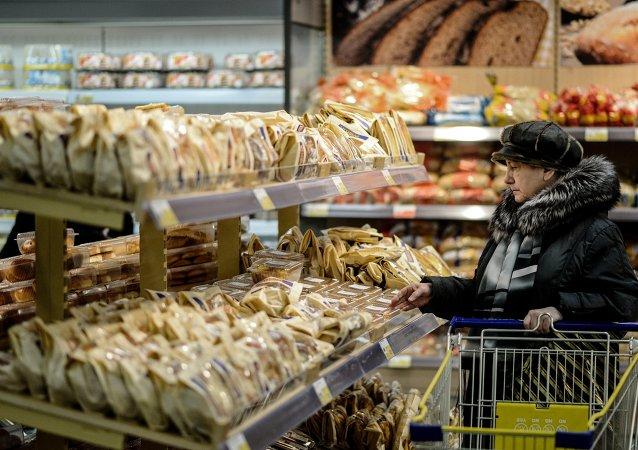 Una mujer compra los productores de pan en un supermercado