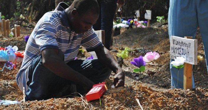 Sobreviviente del virus Ébola llora en la tumba de su hijo en un cementerio para las víctimas de Ébola