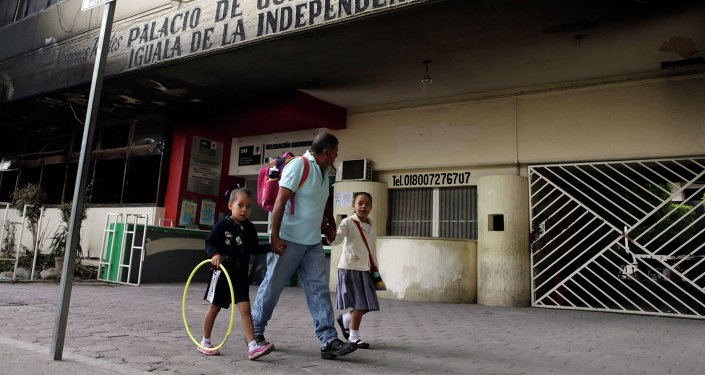 A man walks with his children past outside Iguala's Municipal Palace, in the southwestern state of Guerrero, November 4, 2014.