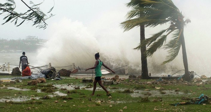Local residents walk past debris as a wave breaks nearby in Port Vila, the capital city of the Pacific island nation of Vanuatu March 14, 2015.