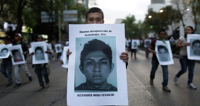 A demonstrator carries a photograph of Alexander Mora Venancio, one of the 43 missing trainee teachers, during a march in support of the students in Mexico City December 6, 2014.