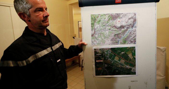 Un bombero francés se encuentra en la escuela secundaria cerca de mapas que muestran la zona en el que Airbus A320 se estrelló en los Alpes franceses