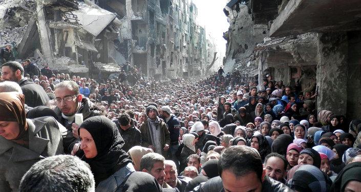 Refugiados palestinos hacen cola para recibir alimentos (imagen referencial)