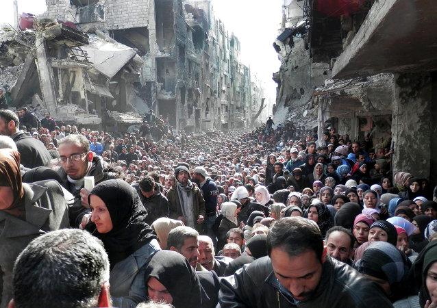 Residentes del campo de refugiados palestinos Yarmuk hacen cola para recibir alimentos (archivo)