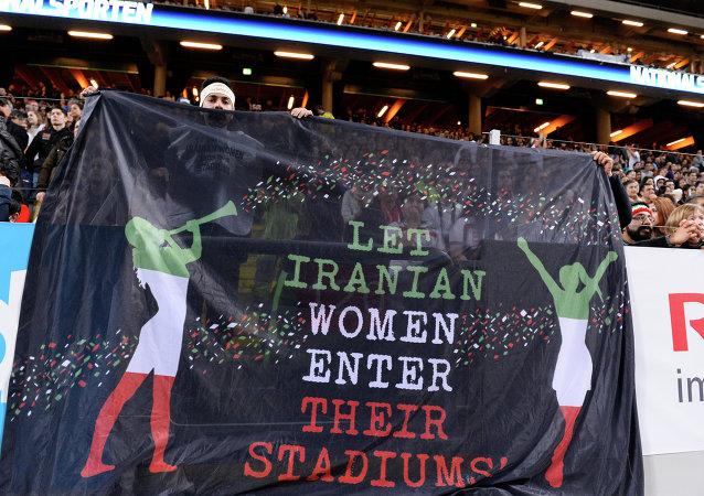 Hinchas sostienen una pancarta que dice 'Que las mujeres iraníes entren en sus estadios' durante el partido amistoso de fútbol entre Suecia e Irán