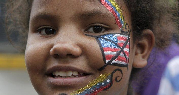 Banderas de Venezuela y EEUU pintados en el rostro de una niña