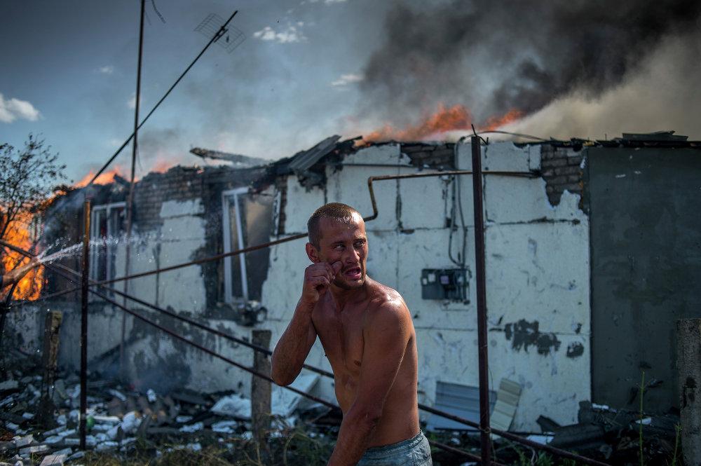 Un habitante local durante la extinción del incendio de una vivienda en el pueblo de Luganskaia, bombardeado por la Fuerza Aérea ucraniana (2 de julio de 2014)