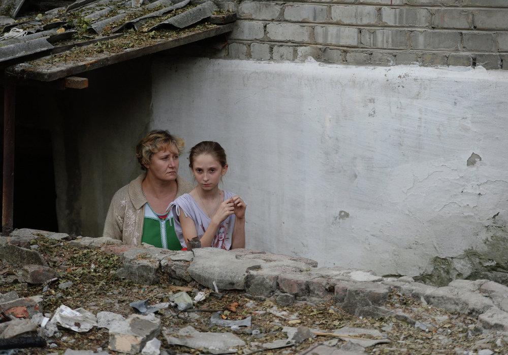Vecinos de la localidad de Ilovaisk junto a la entrada en el sótano donde se refugian durante los bombardeos (14 de agosto de 2014)