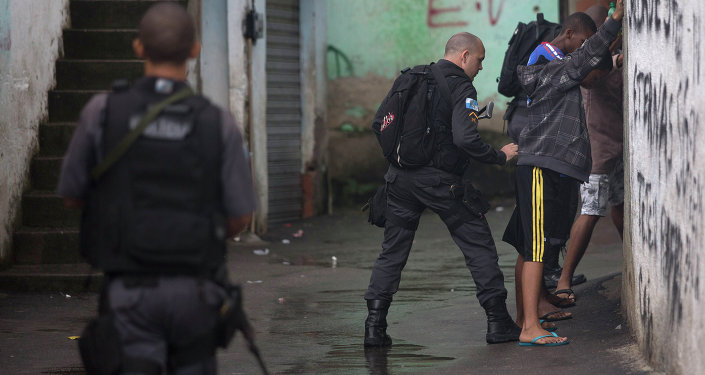 A police officer searches residents in Alemao slum complex as part of a security reinforcement by the UPP (Police Pacification Unit) in Rio de Janeiro