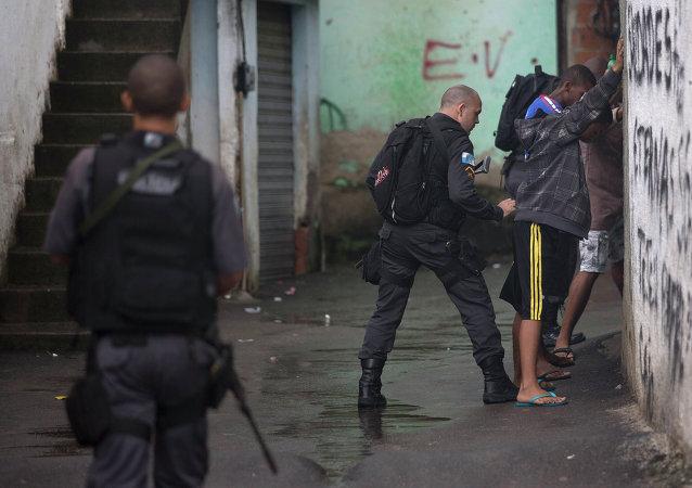 Un agente de policía busca residentes en complejo de Alemao en Río de Janeiro