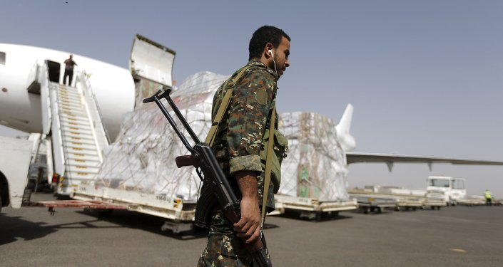 A Houthi militant walks past a shipment of emergency medical aid for the Red Cross being unloaded from a plane at Sanaa airport April 11, 2015.