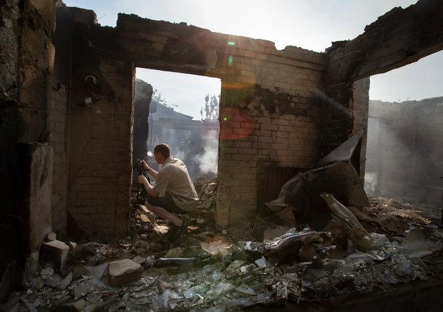Periodista trabaja cerca de una casa destruida tras un ataque en el pueblo Semionovka, este de Ucrania