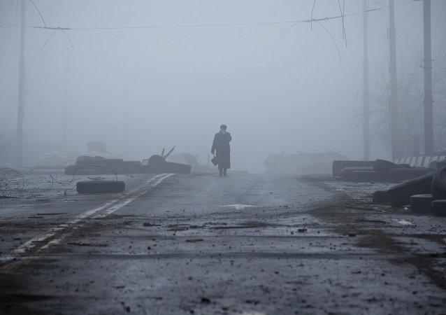 Anciana se acerca un puente destruido en la carretera al aeropuerto de Donetsk