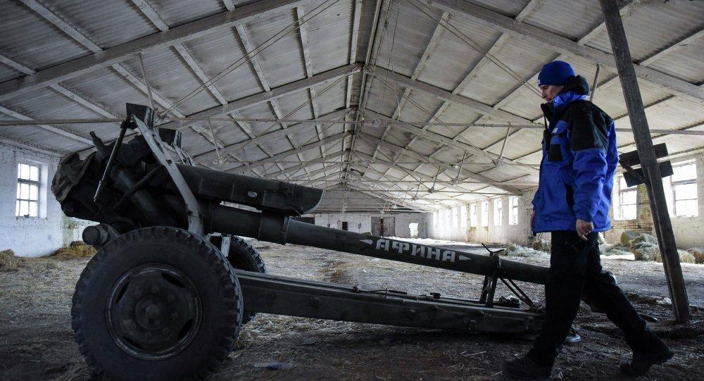 Un agente de OSCE inspecciona el cañón almacenado en Novoamvrosiivska