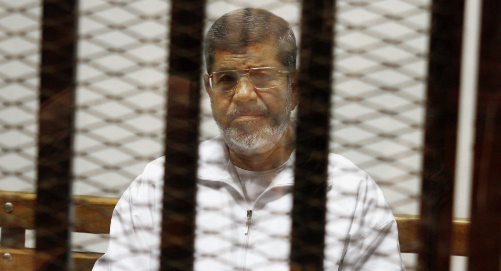 Egypt's ousted Islamist President Mohammed Morsi sits in a defendant cage in the Police Academy courthouse in Cairo, Egypt. On Tuesday April 21, 2015
