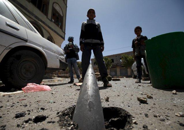 Niños miran a un proyectil  en una de las calles de Saná despues del bombardeo árabe