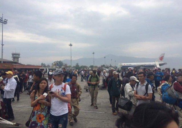 Gente a la pista de la terminal internacional después de un terremoto en Kathmandu