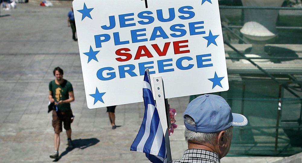 Un hombre lleva una bandera griega y una pancarta que dice Jesús, salva, por favor, a Grecia