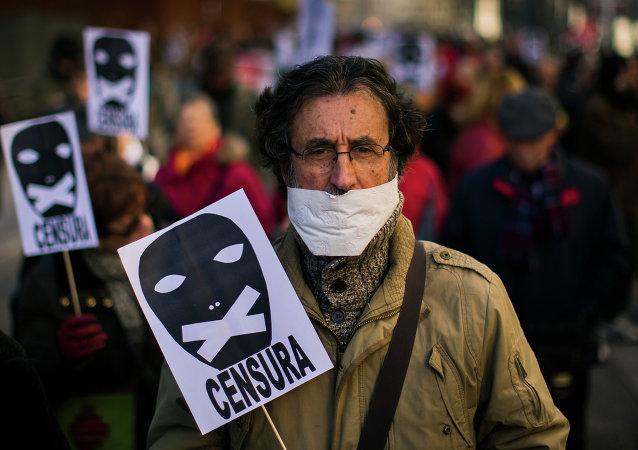 Un hombre sostiene un cartel de censura