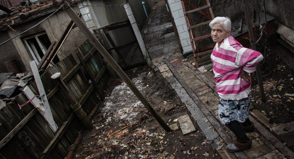 Una anciana delante de su casa destruida por los bombardeos de Donetsk (febrero de 2015)