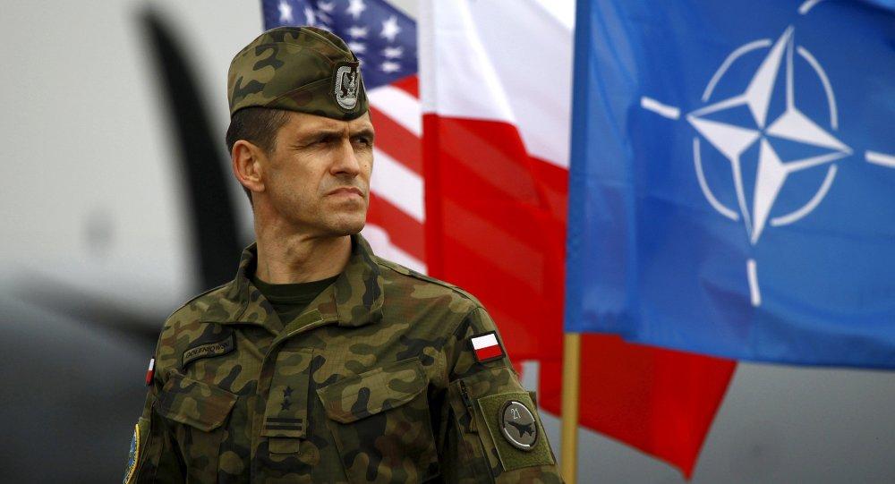 Soldado polaco al lado de las banderas nacionales de los EEUU y Polonia y la bandera de la OTAN