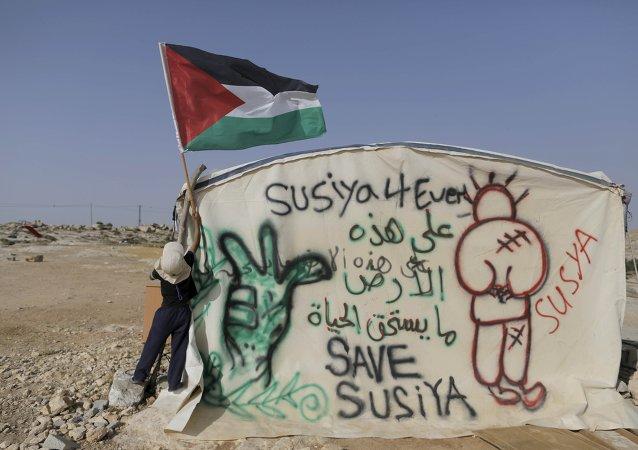 Niño coloca una bandera palestina en una de las casas de Susia. 25 de mayo de 2015