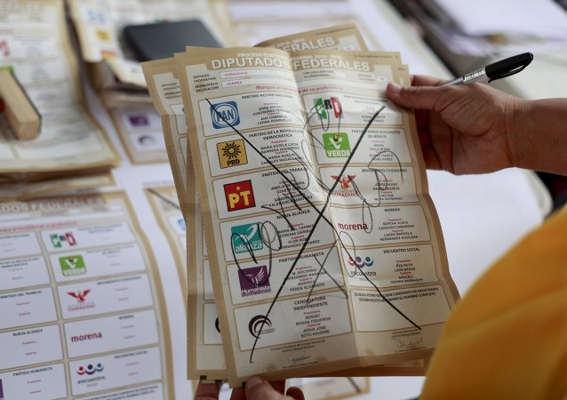 An election official shows a spoilt ballot, with the words 'All corrupt', as votes are counted at a polling station after midterm elections in Ciudad Juarez, Mexico, June 7, 2015